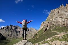 Mulher com a trouxa que caminha no conceito do sucesso do estilo de vida do curso das montanhas fotografia de stock royalty free