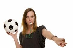 Mulher com um assobio que prende um futebol que aponta a imagens de stock