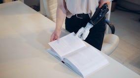 A mulher com um braço biônico está girando páginas de um livro vídeos de arquivo