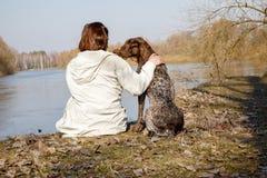 Mulher com um cão que senta-se no banco do rio foto de stock