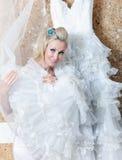 Mulher com um cabelo justo longo que tente sobre um vestido de casamento branco Fotos de Stock