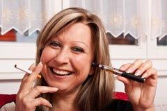Mulher com um cigarro normal e elétrico novos foto de stock