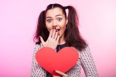 Mulher com um coração vermelho do papper nas mãos Foto de Stock