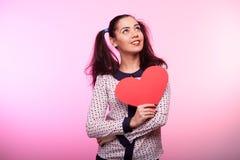 Mulher com um coração vermelho do papper nas mãos Imagens de Stock