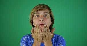 A mulher com um corte de cabelo curto envia um beijo no movimento lento, fundo do chromakey video estoque