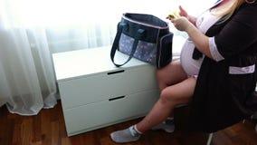 Mulher com um embrião no ventre que prepara-se para o parto que senta-se em casa vídeos de arquivo