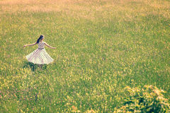 A mulher com um equipamento bonito do vintage está dançando no prado Fotografia de Stock