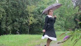 A mulher com um guarda-chuva na chuva levanta à câmera no parque Menina com um guarda-chuva no vestido preto vídeos de arquivo