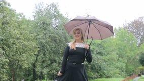 A mulher com um guarda-chuva na chuva levanta à câmera no parque Menina com um guarda-chuva no vestido preto video estoque