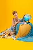 Mulher com um mapa do mundo e os globos Imagens de Stock Royalty Free
