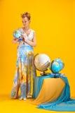 Mulher com um mapa do mundo e os globos Imagens de Stock