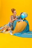 Mulher com um mapa do mundo e os globos Foto de Stock Royalty Free