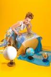 Mulher com um mapa do mundo e os globos Fotos de Stock