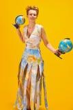 Mulher com um mapa do mundo e os globos Fotografia de Stock Royalty Free