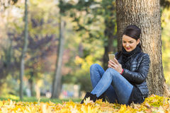 Mulher com um móbil em uma floresta no outono Imagens de Stock Royalty Free