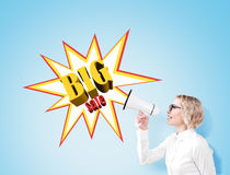 Mulher com um megafone perto de um cartaz grande da venda em uma parede azul Foto de Stock Royalty Free