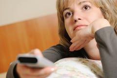 A mulher com um painel de controle da televisão. Imagem de Stock
