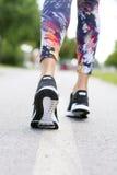 Mulher com um par de sapatas atlético que vão para um movimento ou uma corrida Imagens de Stock Royalty Free
