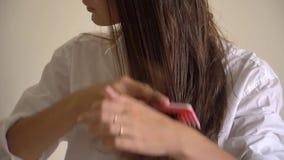 Mulher com um pente em sua mão que escova o cabelo molhado após o banho filme
