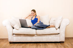 Mulher com um portátil em uma sala de estar fotografia de stock