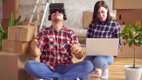 A mulher com um portátil mostra a um homem em vidros da realidade virtual o projeto de um apartamento novo