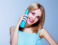 Mulher com um pulverizador de cabelo fotografia de stock