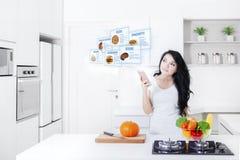 Mulher com um smartphone e umas receitas virtuais fotografia de stock