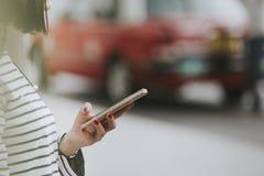 Mulher com um táxi de táxi pedindo do smartphone ou modos da alternativa de transporte Imagens de Stock