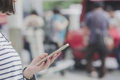 Mulher com um táxi de táxi pedindo do smartphone ou modos da alternativa de transporte Foto de Stock