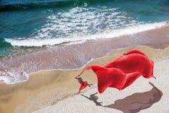 Mulher com um tecido vermelho na praia imagens de stock