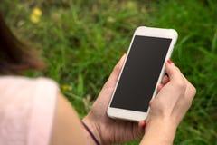 Mulher com um telefone em sua mão fotos de stock royalty free
