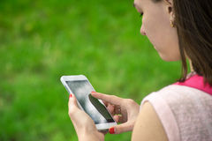 Mulher com um telefone em sua mão fotografia de stock royalty free