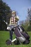 Mulher com um trole e os clubes de golfe Fotos de Stock Royalty Free