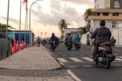 Mulher com um 'trotinette' no homem, Maldivas imagem de stock