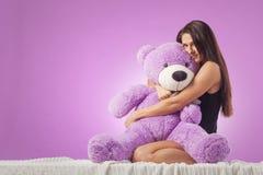 Mulher com um urso de peluche enorme fotografia de stock