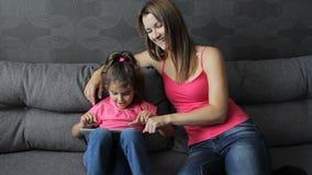 Mulher com um uso da criança uma tabuleta que senta-se no sofá A menina pressiona seu dedo do ` s da mãe na tabuleta Divertimento vídeos de arquivo