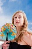 Mulher com um ventilador em um céu azul do fundo Fotografia de Stock