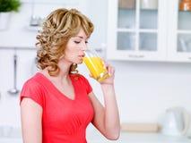 Mulher com um vidro do sumo de laranja fresco Imagens de Stock Royalty Free