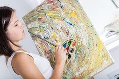 A mulher com uma armação pinta uma imagem Fotos de Stock Royalty Free