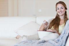 Mulher com uma bacia de pipoca que presta atenção a um filme Imagens de Stock Royalty Free