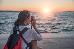 Mulher com uma câmera que fotografa o por do sol na costa de mar fotografia de stock