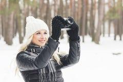 Mulher com uma câmera velha nas mãos, floresta do inverno Fotos de Stock Royalty Free