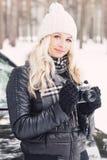 Mulher com uma câmera velha nas mãos, floresta do inverno Imagens de Stock Royalty Free