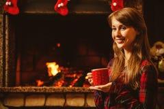 Mulher com uma caneca pela chaminé Mulher atrativa nova Imagens de Stock Royalty Free