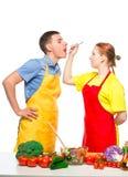 a mulher com uma colher de madeira alimenta a um homem uma salada vegetal útil em um branco imagem de stock