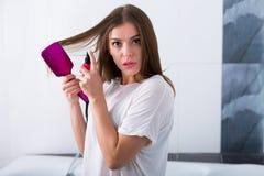 Mulher com uma escova de endireitamento quente foto de stock