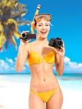 Mulher com uma foto e uma câmara de vídeo na praia imagens de stock royalty free