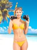 Mulher com uma foto e uma câmara de vídeo na praia fotografia de stock