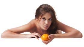 A mulher com uma fruta alaranjada Fotografia de Stock