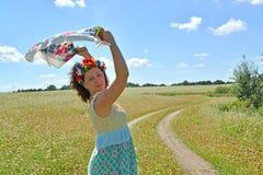 A mulher com uma grinalda na cabeça guarda um lenço colorido nas mãos levantadas na perspectiva do trigo mourisco de florescência Fotos de Stock